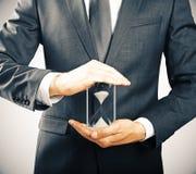 Hållande timglas för affärsman, tidbegrepp royaltyfria bilder