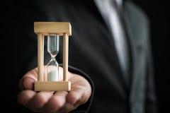 Hållande timglas för affärsmanhand, begrepp för Tid ledning Arkivfoto