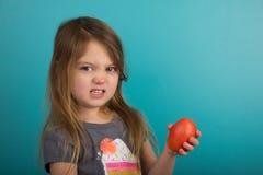 Hållande tomat för liten flicka royaltyfri foto