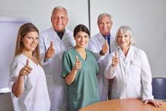 Hållande tummar för doktorslag upp Arkivfoto
