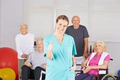 Hållande tummar för fysioterapeut upp framme av den höga gruppen royaltyfri fotografi