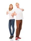 Hållande tummar för lyckliga tonårs- par upp på vit Fotografering för Bildbyråer