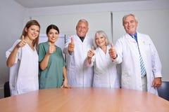 Hållande tummar för medicinskt lag upp Royaltyfria Bilder