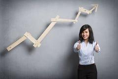 Hållande tummar för nöjd affärskvinna upp framme av det stigande diagrammet Fotografering för Bildbyråer