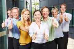 Hållande tummar för vinnande lag för affärsfolk upp Royaltyfri Fotografi