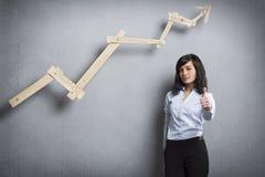 Hållande tumme för nätt affärskvinna upp framme av det positiva affärsdiagrammet Royaltyfri Foto