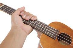 Hållande ukulele för hand på isolerad vit bakgrund Royaltyfri Foto