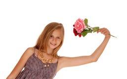 Hållande upp två rosor för älskvärd flicka Royaltyfri Bild