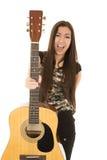Hållande upphetsad kvinnlig modell ut hennes akustiska gitarr Arkivfoto