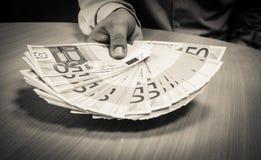 Hållande ut femtio euroräkningar för affärsman över ett skrivbord royaltyfria bilder