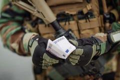 Hållande ut kassa för kommandosoldater 500 euroräkningar Royaltyfri Fotografi