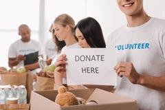 Hållande välgörenhetplakat för volontär arkivbild