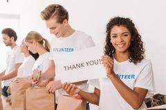 Hållande välgörenhetplakat för volontär fotografering för bildbyråer