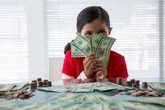 Hållande valuta för lycklig flicka på skrivbordet i regeringsställning royaltyfri fotografi