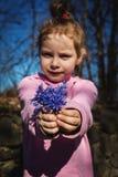 Hållande vildblommor för flickabarn royaltyfri bild