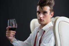 Hållande vinexponeringsglas för androgyn man mot svart bakgrund Royaltyfri Bild