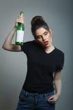 Hållande vinflaska för berusad kvinna Arkivbild