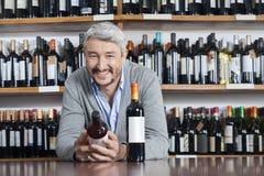 Hållande vinflaska för lycklig man, medan luta på tabellen arkivfoto