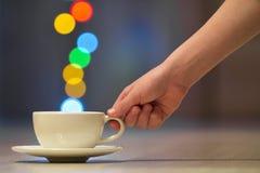 Hållande vit kopp kaffe för hand med färgrik bokehånga royaltyfri bild