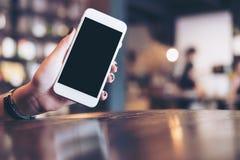 Hållande vit mobiltelefon för hand med mellanrumssvartskärmen i kafé arkivfoton