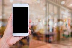 Hållande vit mobiltelefon för hand med mellanrumssvartskärmen på blurr Royaltyfria Foton