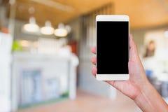 Hållande vit mobiltelefon för hand med mellanrumssvartskärmen på blurr Royaltyfri Fotografi