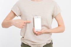 Hållande vit telefon för flicka Mobiltelefon som inom isoleras på den vita snabba banan card grund shopping för dof-fokushanden o Arkivbild