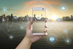 Hållande vit telefon för hand med stadsscape Arkivfoto