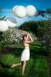 Hållande vita heliumballonger för härlig rolig kvinna, fotografering för bildbyråer