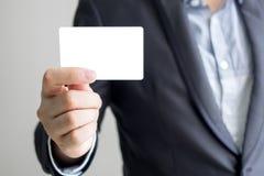 Hållande vitt affärskort för man fotografering för bildbyråer
