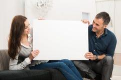 Hållande vitt teckenplakat för par royaltyfria bilder