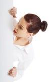 Hållande vitt tomt baner för förvånad kvinna Royaltyfria Bilder