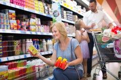 Hållande yoghurt för kvinna från kylskåpet royaltyfri bild