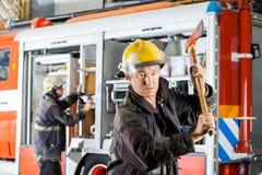 Hållande yxa för säker brandman mot lastbilen Arkivfoton