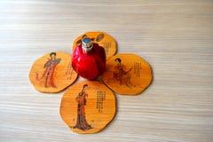 Hållare för kopp te fyra från bambus och en röd flaska av parfume i mitt royaltyfri bild