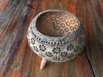 Hållaren som kan användas till mycket som göras från, snider kokosnötskalet, design för blommamodell, på trätabellen royaltyfri foto
