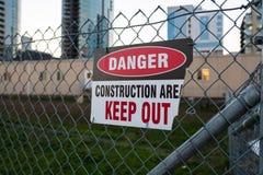 'Håller fara, ut, det konstruktionsområdes'tecknet på staketet arkivfoto