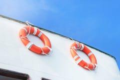 Håller flytande orange liv för säkerhet säkerhetsutrustning på det vita färjaskeppet arkivbild
