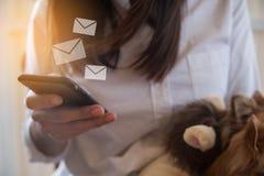 Hållmobiltelefonen för den unga kvinnan och överför emailen, affärsidé Arkivbilder
