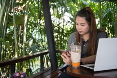 Hållsmartphone för ung kvinna i kaffekafé, den vita bärbara datorn och is Arkivfoto