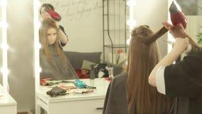 Hår för hairstyling för frisördanandekvinna långt med torken och brushfrontspegeln i loge Slut upp hairstyling arkivfilmer