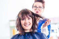 Hår för kvinnan för frisörslaget shoppar torrt in Arkivfoto