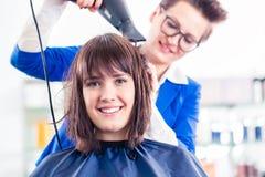 Hår för kvinnan för frisörslaget shoppar torrt in Royaltyfri Fotografi