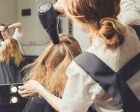 Hår för ` s för kvinna för kosmetologslag torrt på skönhetsalongen royaltyfria bilder