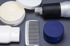 Hår som utformar produkter med hårkammen på grå bakgrund arkivbild
