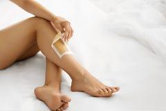 Hårborttagning Långa kvinnaben med vaxremsan på Depilation royaltyfri bild