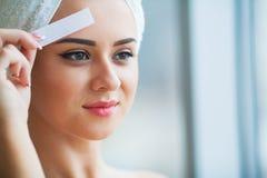 Hårborttagningsvax Ung kvinna som reciving ansikts- epilation fotografering för bildbyråer