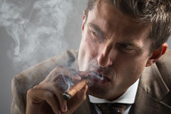 Hård blickaffärsman, medan röka en kubansk cigarr Royaltyfri Fotografi