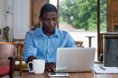 Hård funktionsduglig afrikansk amerikanman med bärbara datorn royaltyfri bild