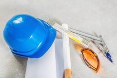 Hård hatt, exponeringsglas och ritningar på konstruktionsplatsen Royaltyfri Foto